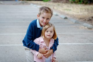 A photo of an older brother with his arms around his younger sibling sister who has a developmental disability.