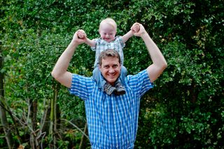 Father holds his toddler with disabilities on his shoulders.