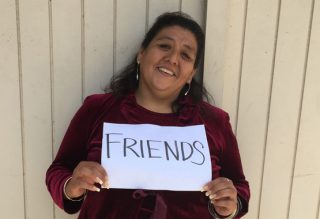 woman holds friends sign