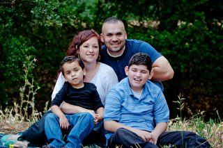 Portrait of family of four in the park, one child has a developmental disability.