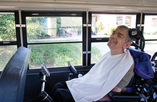 man is wheelchair on bus