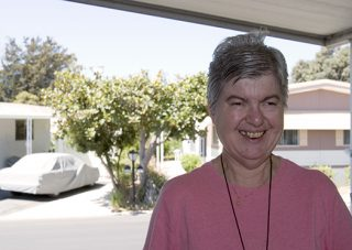 A senior woman smiles from the porch of her mobile home.