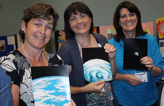 A photo of three people holding pictures of different views of the earth as seen from space while at the California Gathering.