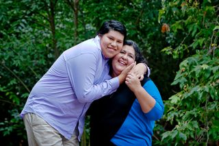 A portrait photo of a boy standing next to his mother holding her face close to his in a park. Both are smiling.