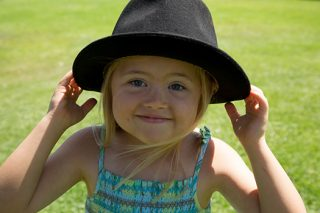 Young girl plays after stealing her Father's hat.