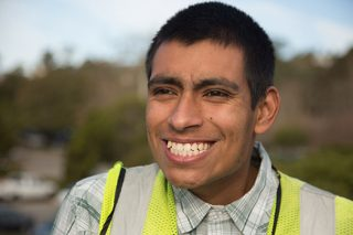 Young man wearing a safety vest with a big white smile while he works in group employment.