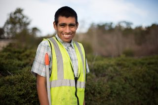 Young man with autism poses during landscape work with his team.