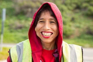 A woman in group employment wearing a safety vest, and a red hoodie, showing a big white smile.