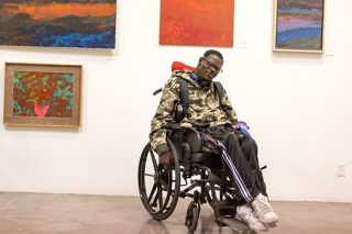 Man with cerebral palsy poses in an art gallery where he is employed.