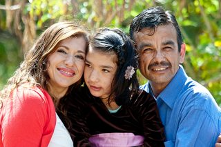 Mom and dad hold daughter with development disabilities in the park.