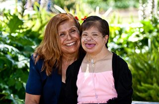Mother smiles with her adult daughter with down syndrome.