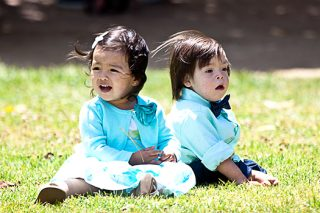 Two siblings in pale blue sit together on the lawn, one with down syndrome.