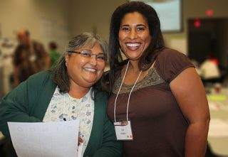 A photo of two women with their arms around each other looking at the camera while at the California Gathering.