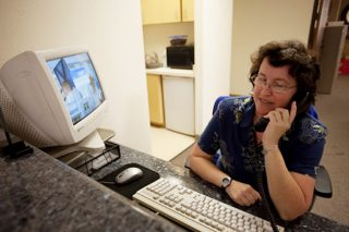 A woman with special needs answers the phone at her office assistant job.