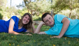 Sister and brother, lay on their sides on the grass and smile.