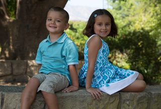 Brother and sister pose on a cobblestone bench.