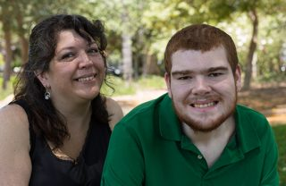 Mother smiles with her son, a young adult with autism.