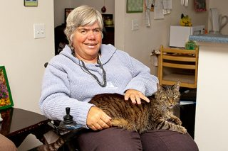 A woman in independent living enjoys her cat, who likes to sit on her lap when she is in her wheel chair.