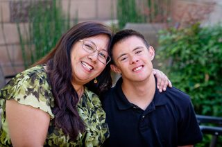 Mother smiling with her smiling teenage son that has a developmental disability.