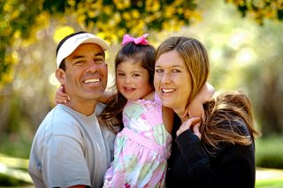 Father and mother hold daughter in between for Fall family portrait.