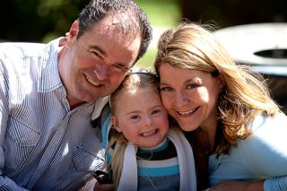 Mom and dad pose with daughter with down syndrome in the middle.
