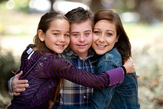 Three siblings, all in hugging together and smiling.