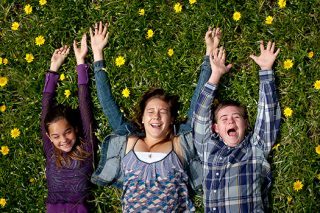 A photo of three young kids laying down in the green grass laughing while their arms are stretch up over their heads as if they are flying.