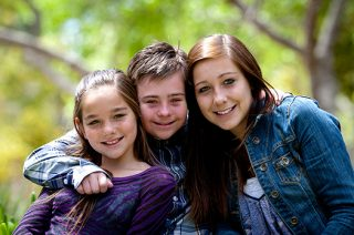 A boy with down syndrome smiles in between his two sisters while he has his arms around both of them.