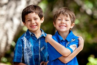 A photo of two young boys wearing bright blue shirts and big smiles while standing near a creek bed.