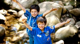 A photo of two young boys with their arms open wide wearing bright blue shirts and big smiles while standing near a creek bed.