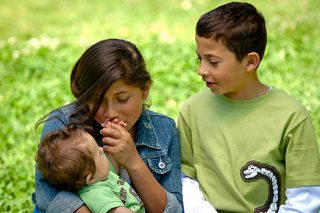 Sister lovingly kissing the hand of an infant that is in her arms as older brother next to them looks on.