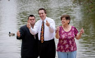 Three friend with developmental disabilities give thumbs up, while standing on the shore of a duck pond.