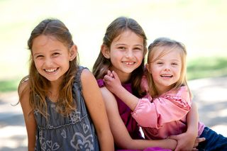 A photo of three young sisters sitting in the park smiling and laughing.