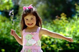 A young girl in a patchwork sun dress smiling while walking in the park holding a flower in her hand.