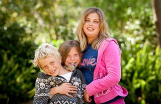 A photo of an older sister holding two smiling siblings in the park.