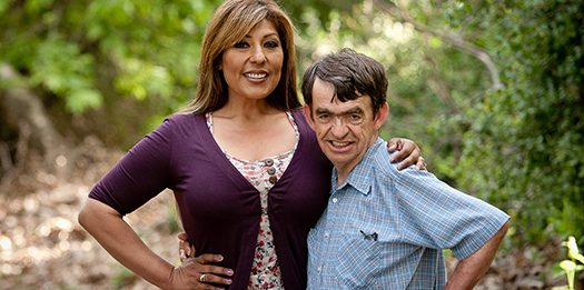 A photo of a woman standing with her arm around a man that has a developmental disability, arms akimbo both smiling.
