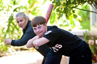 A young man with down syndrome, in a baseball jersey holding a baseball bat practicing to receive a pitch.