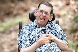 A man with cerebral palsy smiling while sitting in a wheel chair.