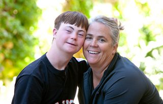 A portrait photo of a woman with her arm around a child with a developmental disability. They are both smiling.