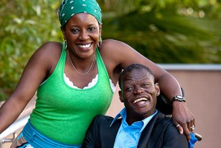 A photo of a woman, with her arm around a man in a wheel chair. Both have wonderful smiles.