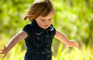 Toddler girl spins with her arms out in the sunshine.