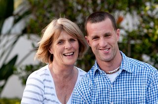 Wind blows back the hair of mother who smiles with her adult son with disabilities.