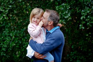 A portrait photo of a father holding his young daughter in his arms while kissing her cheek.
