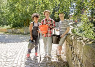 Three young people in casual clothes holding buckets for water on a cobble stone walkway ready to gather produce for the farm cafe.